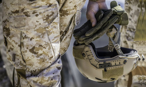 Military personnel holding a combat helmet