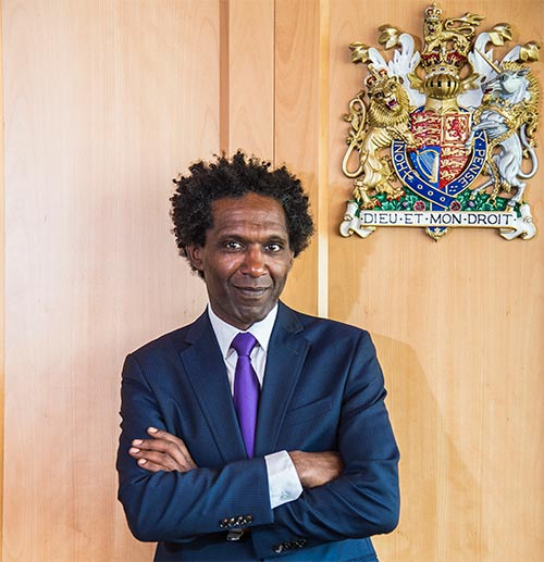Lemn Sissay in front of the crest in the moot room