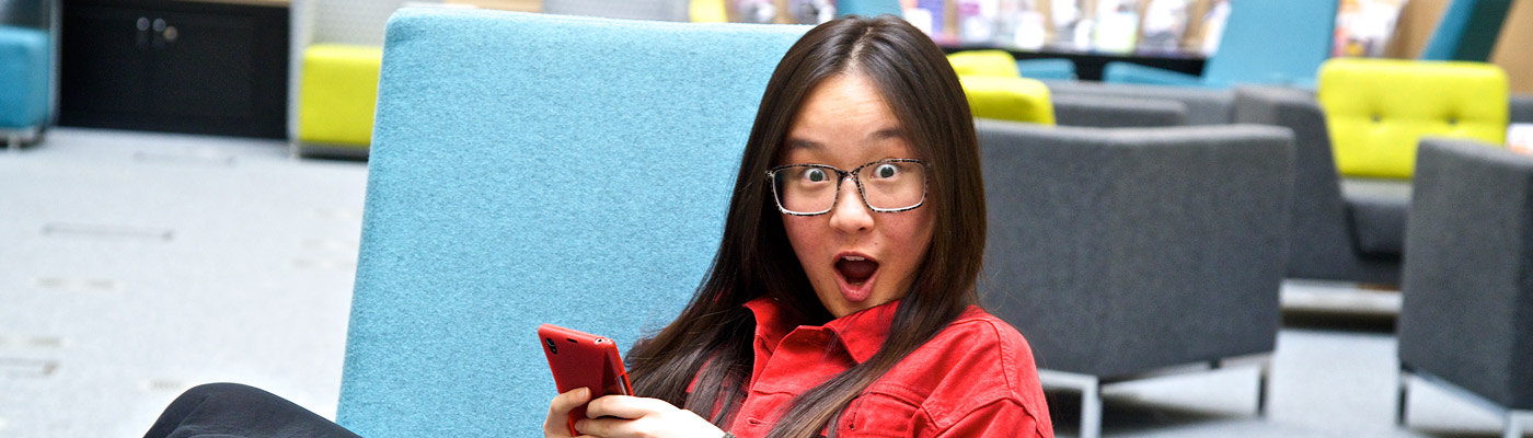 Student with a surprised look on her face holding a mobile phone.