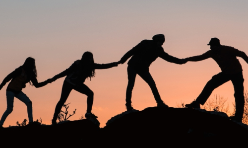 Four people holding hands on a hill at sunset
