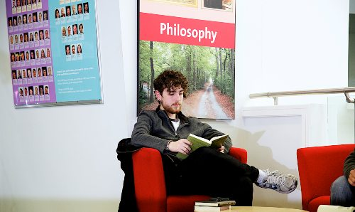 Male philosophy student sat reading a book in front of 'philosophy' sign.