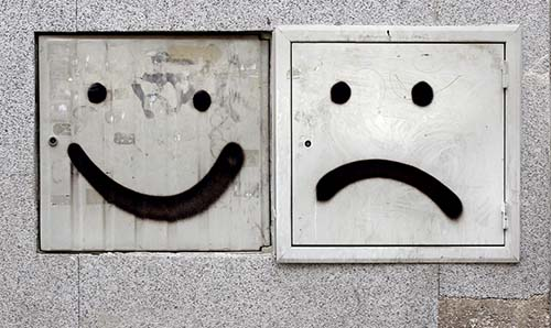 Graffiti faces (happy and sad) on square electrics boxes