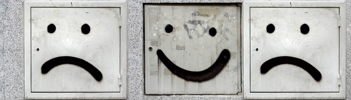 graffiti showing smiley and sad faces