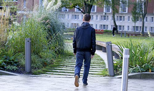 male student walking through campus grounds